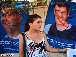 A Hezbollah militant in 2007 puts a flag on a billboard bearing photographs of two kidnapped Israeli soldiers.