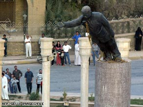 Iraqis watch as a statue of Saddam Hussein is toppled in Baghdad in 2003.