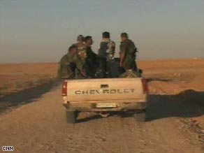 Syrian soldiers in a pickup truck patrol the area of their country's border with Iraq.