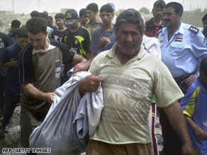 An exhumed body is carried away from a school being built  in Ramadi, Iraq.