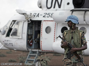 A Rwandan soldier serving with the U.N.-African Union peacekeeping force in Darfur guards a U.N. helicopter.