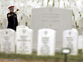 A U.S. Army bugler plays taps during burial services for a female soldier at Arlington National Cemetery in 2005.
