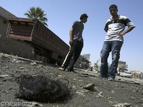 An Iraqi man examines a tuft of human hair at the site of a suicide bombing in northern Baghdad on Monday.