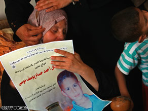 Maysaloun Moussa, mother of the slain boy, holds a poster bearing his image at her home Wednesday.