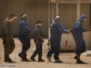 Fatah members are led handcuffed and blindfolded through a Gaza City checkpoint into Israel on Saturday.