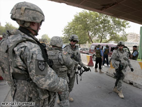 U.S. troops patrol near a checkpoint in Baghdad last week.