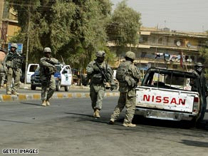 U.S. soldiers secure the site of a car bomb explosion that killed two people Monday in Baghdad.