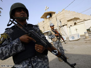 Iraqi policemen patrol Tuesday outside a Christian church in the Baghdad district of Dora.