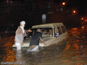 Men try to reach a vehicle carrying tourists stranded in floodwaters in the old district of Sanaa Friday.