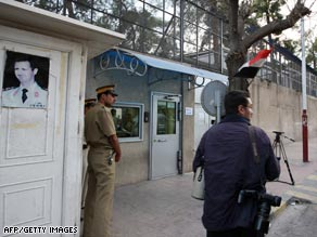 Guards stand outside the American school in Damascus on Tuesday. Syria says it will close the school.