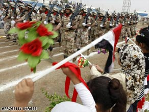 Girls wave at Iraqi soldiers during a parade in Kut to mark the transfer of Wasit province to Iraqi control.