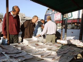 Iraqis scan newspaper headlines in Baghdad on Wednesday.