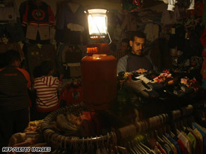 Palestinians shop by the light of a gas lamp amid electricity shortages in Gaza City on Thursday.