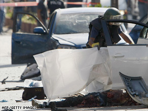 Police at the scene of the car bomb blast which killed crime boss Yaakov Alpheron.
