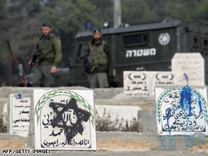 Israeli soldiers guard a Muslim cemetery Thursday in Hebron after Jewish settlers vandalized gravestones.