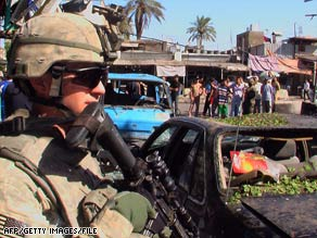 A U.S. soldier keeps watch at the scene of a suicide bombing in Baghdad, Iraq, this month.