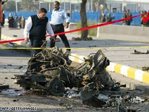 An Iraqi policeman inspects the scene of a car bombing near a police academy in Baghdad on Monday.