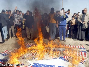 Shiite Muslims burn a replica of the American flag in the Sadr City district of Baghdad on Friday.
