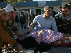 A wounded woman receives care after a suicide bombing Thursday outside Kirkuk, Iraq.