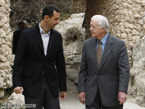 Syrian President Bashar al-Assad, left, walks with Jimmy Carter north of Damascus on Sunday, December 14.