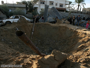 Palestinian children look at a blast crater following an Israeli airstrike over southern Gaza on December 18.
