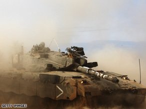 An Israeli tank maneuvers near the Israeli border with Gaza on Sunday near kibbutz Kisufim, Israel.