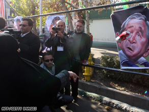 A woman throws a training shoe at a caricature poster of President George W. Bush in Tehran on December 26.
