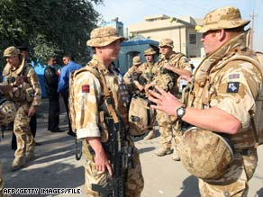 British troops talk in Basra last week. Iraq on Sunday OK'd foreign troops to remain in the country after the new year.