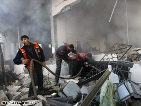 Firefighters work to control a blaze in Gaza City on Monday after an Israeli airstrike.