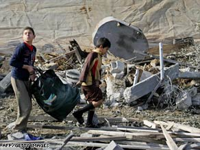 Palestinian boys carry their belongings over the ruins of a house Tuesday after an Israeli airstrike in Rafah.