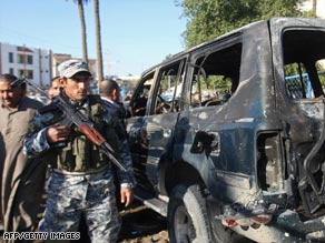 An Iraqi police officer secures the scene of a car bombing Saturday in Baghdad.