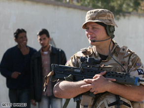 A British soldier stands guard outside as Iraqi teens look on.