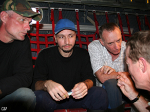 U.S. contractors Keith Stansell, left, Marc Gonsalves, center, and Thomas Howes sit in an aircraft in an unknown location in Colombia after being rescued.