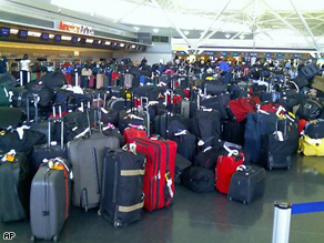 Hundreds of bags wait to be checked at New York's Kennedy Airport Wednesday. The  baggage system was not functioning, delaying some flights and others to take off without baggage.