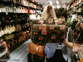 A shopworker in Beijing holds up a handbag based on a Louis Vuitton design.