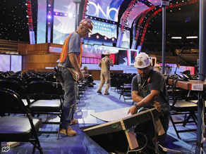 Electricians connect power cable as preparations on the floor of the site of the Democratic National Convention in Denver, Friday. The convention starts Monday, Aug. 25.