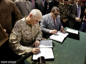 U.S. Marine Maj. Gen. John Kelly and Anbar Province Governor Maamoun Sami Rashid al-Alwani sign papers during a handover ceremony in Ramadi, Monday.