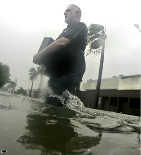 A man clutches a brief case as he makes his way through high water created by hurricane Ike's storm surge in downtown Galveston, Texas