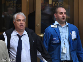 Employees leave the New York Stock Exchange on Friday after a tumultuous week.