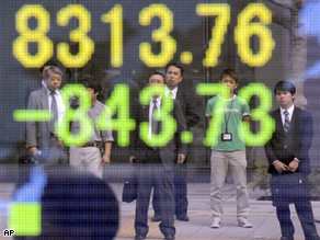 Pedestrians watching market information are reflected in an electric signboard in Tokyo, Friday. Japanese shares nose-dived more than 10 percent in morning trade Friday as panicked investors dumped stocks following massive overnight losses on Wall Street and on growing fears over a global recession.