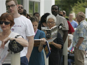 People stand in line to vote early Wednesday in Pompano Beach, Fla. Unprecedented numbers of early voters in the South are prompting local election officials to take measures to make people comfortable as they wait for hours to cast their ballots.