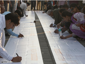 People sign messages of condolence on a banner in memory of those killed in the recent terror attacks in Mumbai.