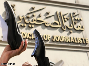 Sympathizers of Iraqi TV reporter Muntadhar al-Zaidi hold their shoes in the air while participating in a support rally.