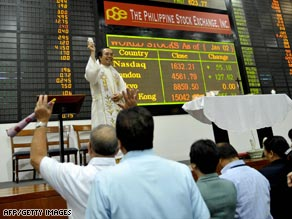 A priest officiates a mass at the Philippine Stock Exchange Monday.