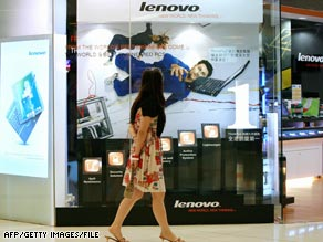 A woman walks past a Lenovo advertisement at a computer shop in Hong Kong.