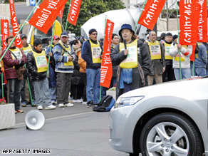 Honda workers protest Tuesday's production cuts outside the car company's HQ in Tokyo.