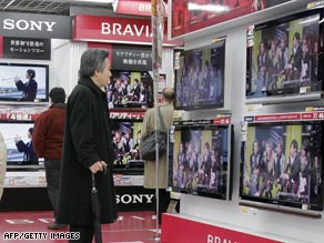 Customers check Sony's Bravia brand LCD TVs at an electronics shop in Tokyo, Japan.