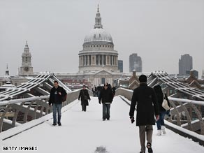 Pedestrians cross the Thames in front of St Paul's Cathedral in London's financial district.
