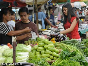 Customers buy vegetables at a market in Quezon City in suburban Manila, Philippines, on September 16.