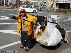 A homeless man pulls his cart filled with possessions and goods for recycling on March 18 in Osaka, Japan.